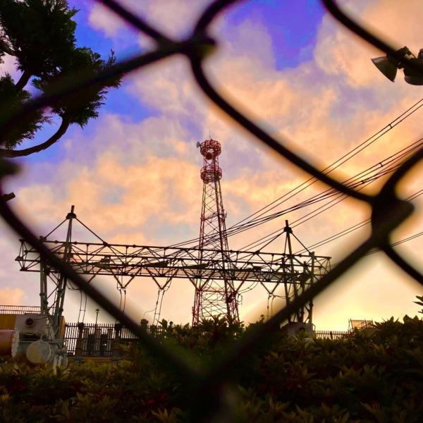フェンス越しの鉄塔風景